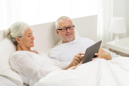 pareja en la cama: familia, la tecnología, la edad y el concepto de la gente - la feliz pareja senior con ordenador Tablet PC mentira de mala en casa Foto de archivo