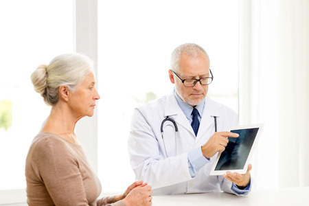 roentgen: medicine, age, health care and people concept - senior woman and doctor with tablet pc computer meeting in medical office Stock Photo