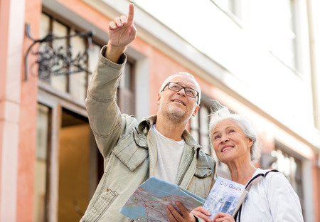 travel guide: family, age, tourism, travel and people concept - senior couple with map and city guide on street