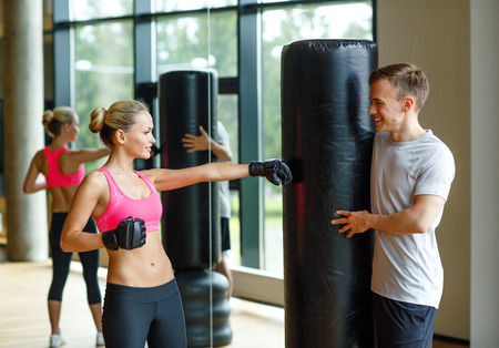 punching bag: sport, fitness, lifestyle and people concept - smiling woman with personal trainer boxing in gym