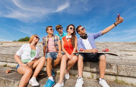 Having Fun: friendship, leisure, summer, technology and people concept - group of smiling friends with skateboard and smartphone making selfie outdoors