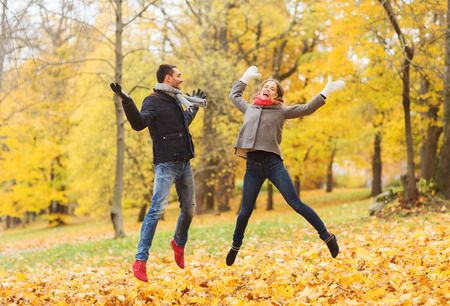 people having fun: love, relationship, family and people concept - smiling couple having fun in autumn park Stock Photo