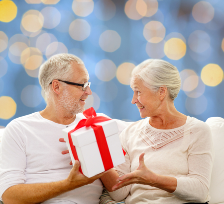 family sofa: family, holidays, christmas, age and people concept - happy senior couple with gift box over blue lights background