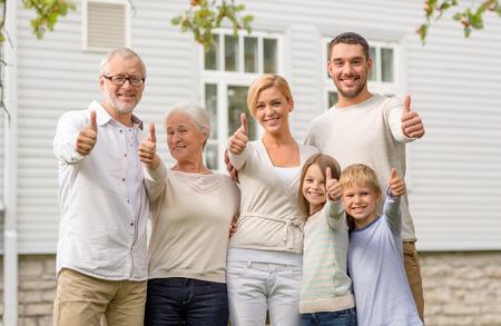 familias felices: familia, la felicidad, la generaci�n, el hogar y las personas concepto - la familia feliz que se coloca delante de la casa al aire libre Foto de archivo