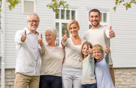 3 generation: family, happiness, generation, home and people concept - happy family standing in front of house outdoors Stock Photo