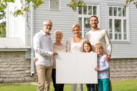 familia, la felicidad, la generación, el hogar y las personas concepto - familia feliz de pie delante de la casa con la tarjeta en blanco blanca al aire libre