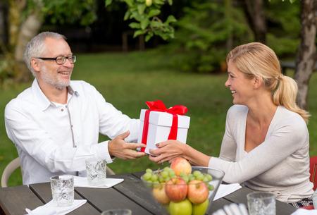 högtider: familj, lycka, generation, hem och folk koncept - lycklig familj med presentförpackning med semester middag utomhus Stockfoto