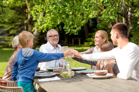 grandmother and children: family, happiness, generation, home and people concept - happy family having holiday dinner outdoors