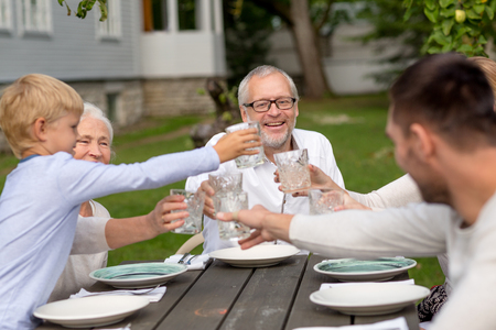 three generation: family, happiness, generation, home and people concept - happy family having holiday dinner outdoors