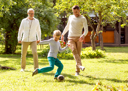 family, happiness, generation, home and people concept - happy family playing football in front of house outdoors Stockfoto