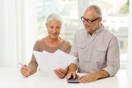 familie, bedrijf, besparingen, leeftijd en mensen concept - lachende senior paar met papieren en rekenmachine thuis