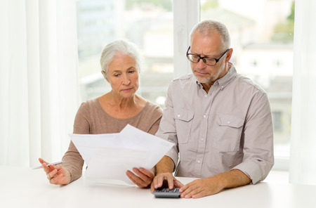 woman with document: family, business, savings, age and people concept - senior couple with papers and calculator at home