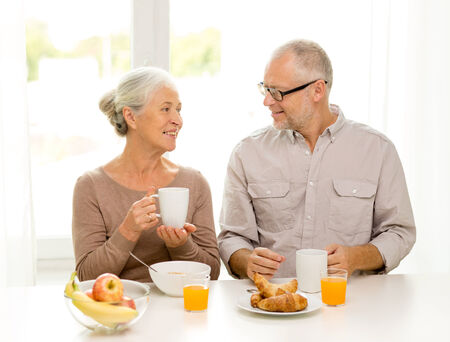 family, technology, food, drinks and people concept - happy senior couple having breakfast at home photo