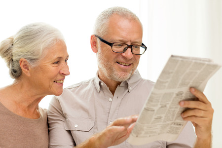 family, holidays, age and people concept - happy senior couple reading newspaper at home