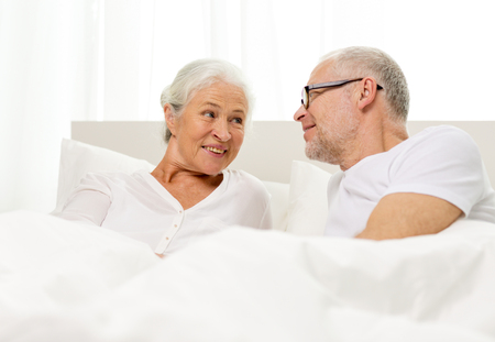 family, bedtime, resting, age and people concept - happy senior coupler lying in bad at home photo