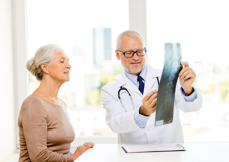 roentgen: medicine, age, health care and people concept - smiling senior woman and doctor meeting in medical office