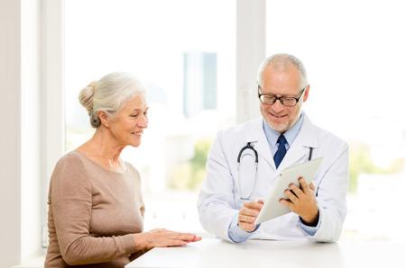vecchiaia: la medicina, l'et�, l'assistenza sanitaria e la gente concept - maggiore sorridente donna e medico con la riunione del computer tablet pc in ufficio medico