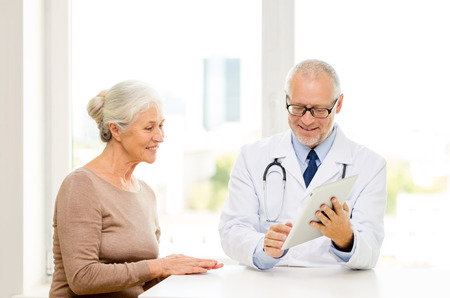 doctor and patient: medicine, age, health care and people concept - smiling senior woman and doctor with tablet pc computer meeting in medical office