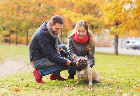 mujer con perro: cuidado, los animales, la familia, la temporada y la gente concepto - sonriente pareja con el perro en parque del oto�o