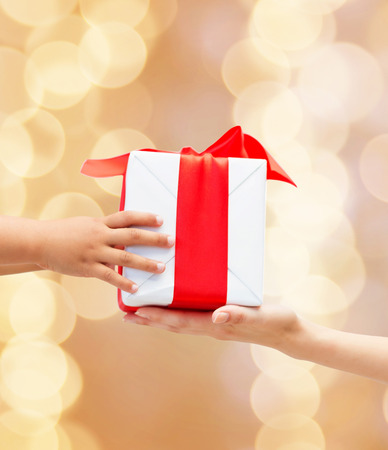gift giving: holidays, present, christmas, childhood and happiness concept - close up of child and mother hands with gift box over beige lights background