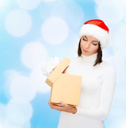 christmas, winter, happiness, holidays and people concept - woman in santa helper hat with gift box over blue lights background photo