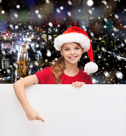 christmas, holidays, people, advertisement and sale concept - happy little girl in santa helper hat with blank white board over snowy night city background photo