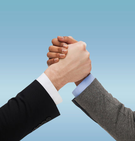 business, people, international and competition concept - close up of two hands multiracial armwrestling or handshake over blue background photo
