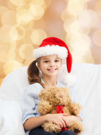 holidays, presents, christmas, childhood and people concept - smiling little girl with teddy bear toy over beige lights background photo