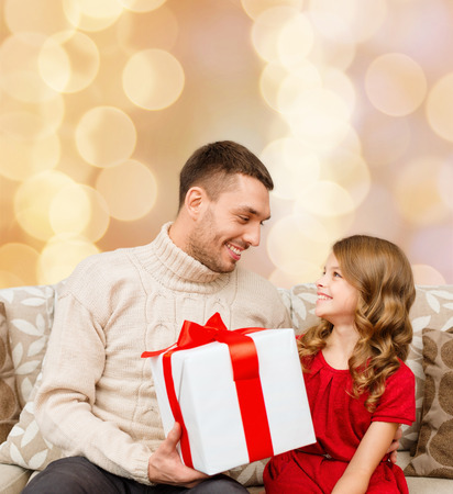 birthday present: family, christmas, holidays and people concept -smiling father and daughter with gift box over beige lights background Stock Photo
