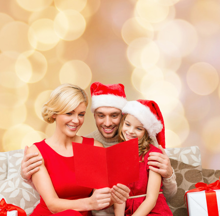 christmas, holidays, family and people concept - happy mother, father and little girl in santa helper hats with gift boxes reading geeting card over beige lights background photo