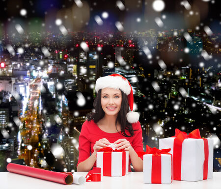 christmas, holidays, celebration, decoration and people concept - smiling woman in santa helper hats with decorating paper and gift boxes over snowy night city background photo