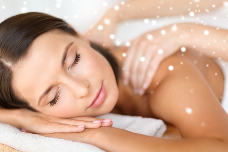 beauty, health, holidays, people and spa concept - beautiful young woman in spa salon getting massage
