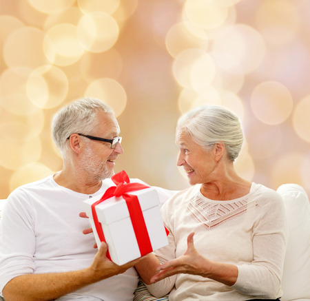 family, holidays, christmas, age and people concept - happy senior couple with gift box over beige lights background photo