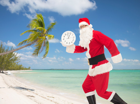 twelve month old: christmas, holidays and people concept - man in costume of santa claus running with clock showing twelve over tropical beach background Stock Photo