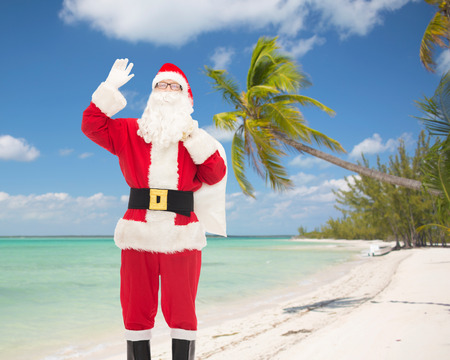 christmas, holidays, gesture and people concept - man in costume of santa claus with bag waving hand over tropical beach background photo