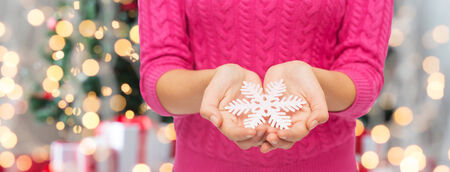 christmas, holidays and people concept - close up of woman in pink sweater holding snowflake over tree lights background photo