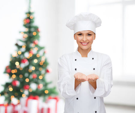 christmas cooking: cooking, advertisement, holidays and people concept - smiling female chef, cook or baker holding something on palms of hand over living room and christmas tree background Stock Photo