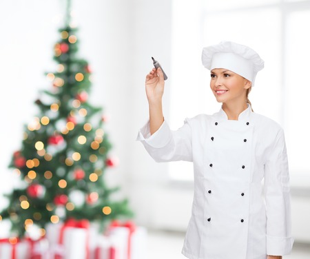 cooking, holidays, advertisement and people concept - smiling female chef, cook or baker with marker writing something on virtual screen over living room and christmas tree background photo
