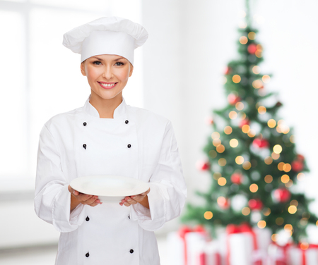 cooking, holidays, people and food concept - smiling female chef, cook or baker with empty plate over living room and christmas tree background photo