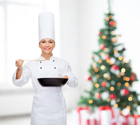 pan asian: cooking, holidays, people and food concept - smiling female chef with pan and spoon tasting food over living room and christmas tree background