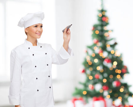 cooking, holidays, holidays, advertisement and people concept - smiling female chef with marker writing something on air over living room and christmas tree background photo