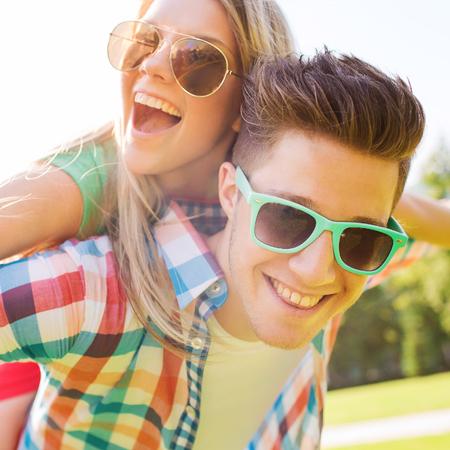 sunglasses: días de fiesta, vacaciones, el amor y el concepto de amistad - sonriente pareja adolescente en gafas de sol que se divierten en el parque de verano