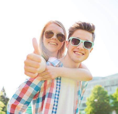 adolescente: vacaciones de verano, vacaciones, amor, el gesto y el concepto de la amistad - sonriente pareja adolescente en gafas de sol que se divierten y mostrando los pulgares para arriba en el parque Foto de archivo