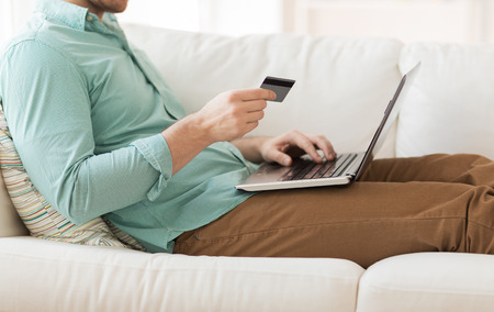 buying online: technology, shopping, banking, home and lifestyle concept - close up of man with laptop computer and credit card at home