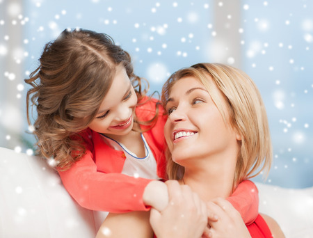 girl bonding: people, motherhood, family, winter and adoption concept - happy mother and daughter hugging at home