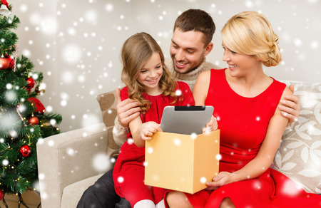 papa noel: christmas, holidays, technology and people concept - smiling family taking tablet pc out from gift box at home Stock Photo