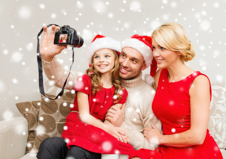 christmas, holidays, technology and people concept - happy family with digital camera taking selfie at home photo