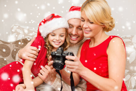 indoor photo: christmas, holidays, technology and people concept - happy family with digital camera watching photos at home