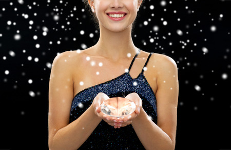 big teeth: people, holidays and glamour concept - close up of smiling woman with diamond over black snowy background