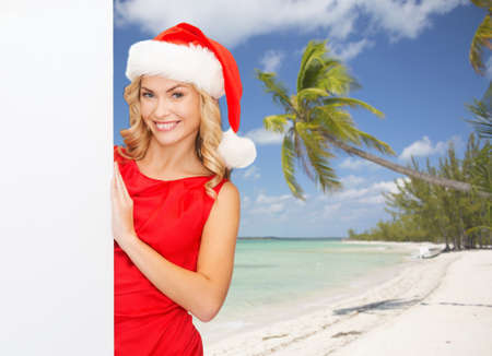 winter holidays, christmas, advertising and people concept - smiling young woman in santa helper hat with white blank billboard over tropical beach background